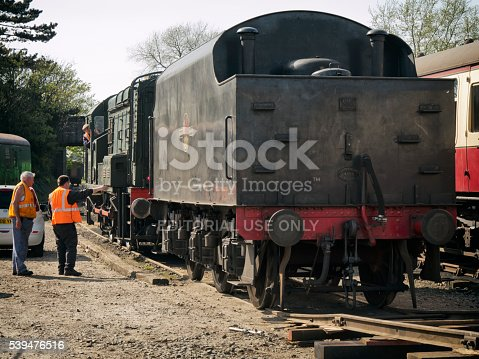 Sheringham, Norfolk, England - May 5, 2016: Two railmen watch while the driver of a diesel shunter engine moves the tender belonging to a steam engine which has just been delivered to the North Norfolk Railway at Sheringham, Norfolk, eastern England. The North Norfolk Railway (also known as the Poppy Line) operates a variety of engines and carriages, both steam and diesel and runs between Sheringham and Holt. The engine is number 45337 of the LMS Stanier Class and the photograph was taken in the public car park behind the station.