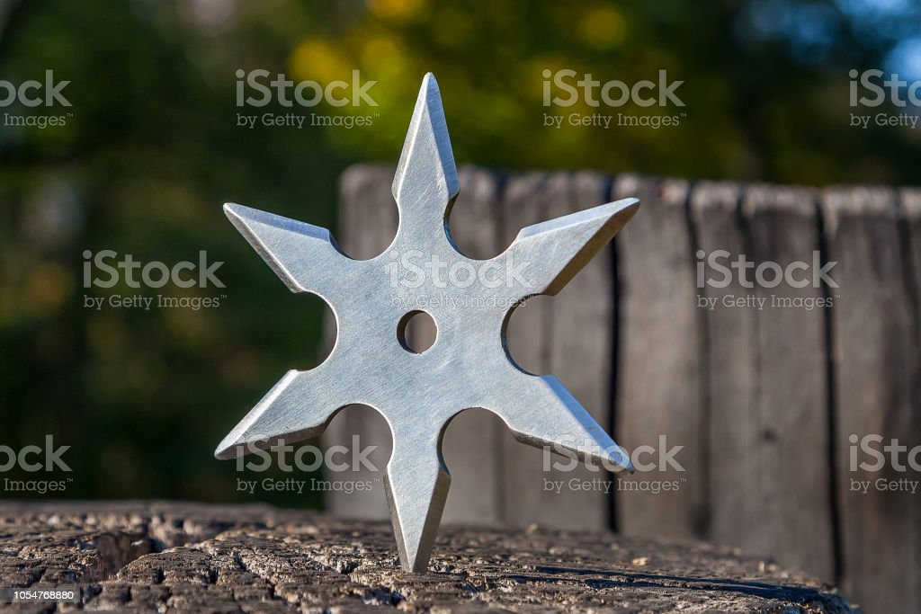 Shuriken (throwing star), traditional japanese ninja cold weapon stuck in wooden background stock photo