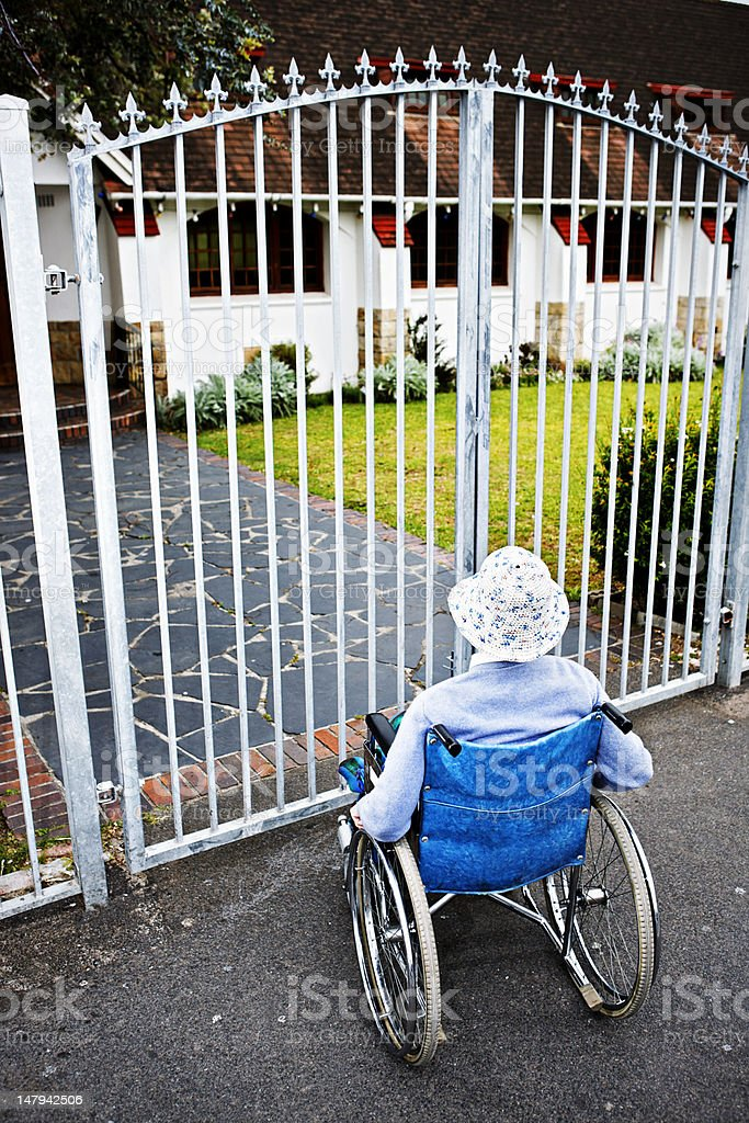 Shut out, a wheelchair bound woman cannot get through gates royalty-free stock photo