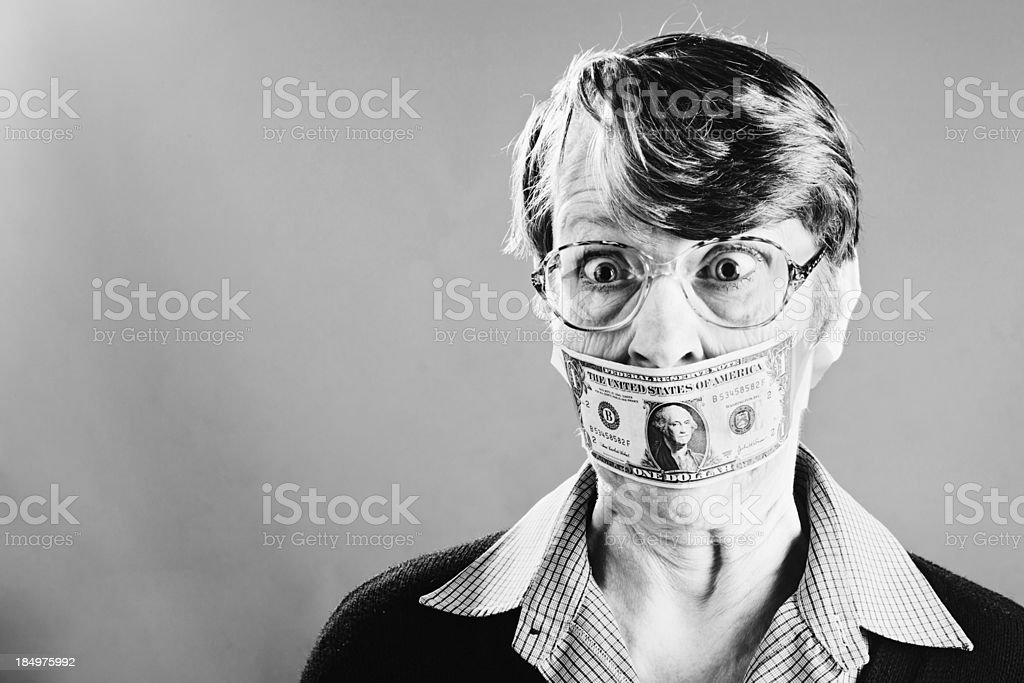 Shut up! Outraged old woman is gagged by dollar bill stock photo
