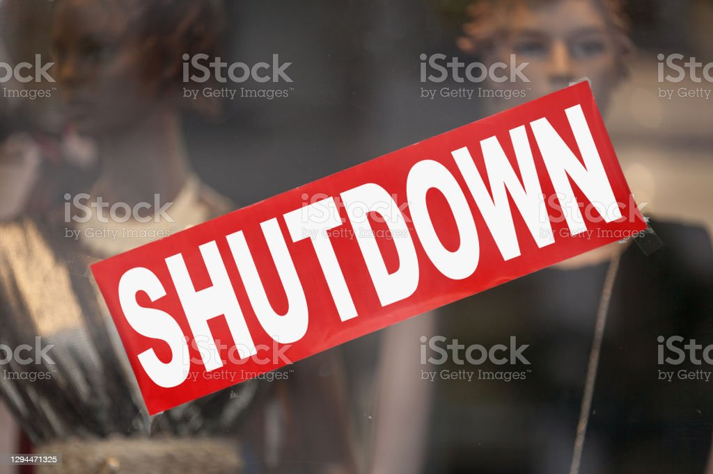 "Shutdown - Closed sign Red sign in a window shop saying in ""Shutdown"". Bankruptcy Stock Photo"