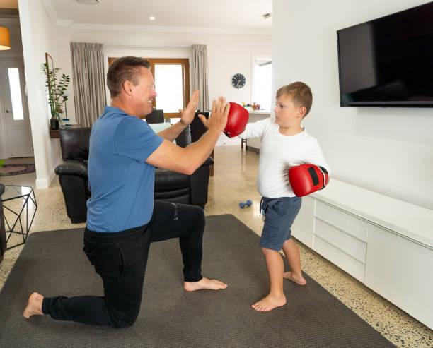 COVID-19 Herunterfahren. Vater und Sohn haben Spaß beim gemeinsamen Boxen und bleiben während der Coronavirus-Quarantäne körperlich aktiv. Bleiben Sie zu Hause, Übung, Gesundheit Selbstversorgung für Coronavirus Isolierung. – Foto
