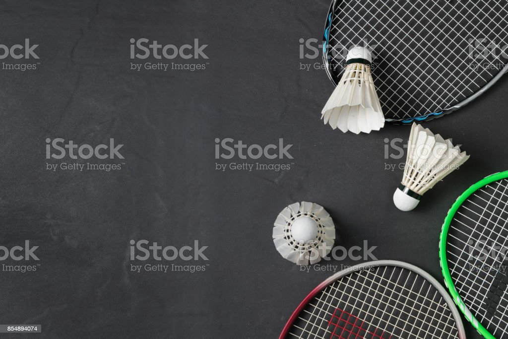 Shuttlecocks and badminton racket on black background. – zdjęcie