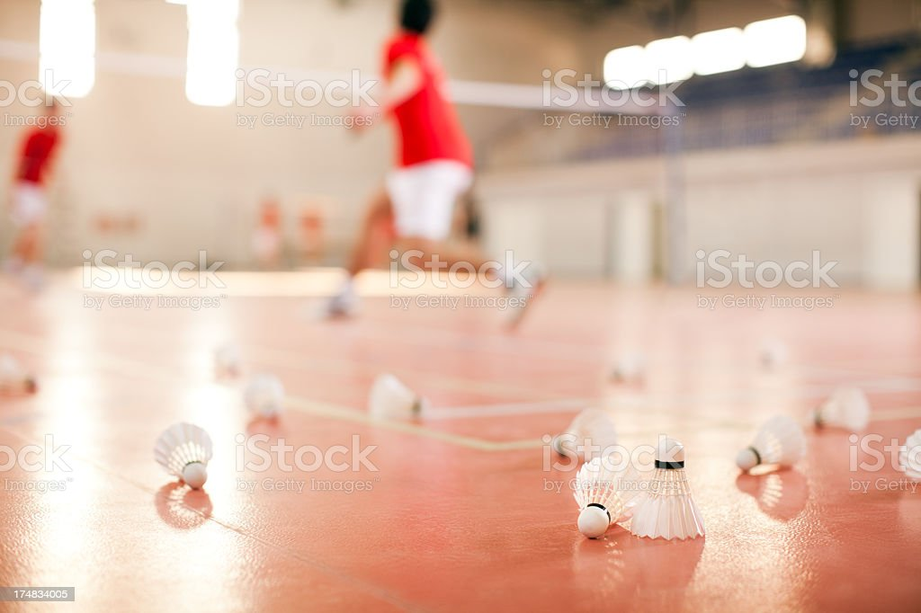 Shuttlecocks on the floor next to blurred badminton players stock photo