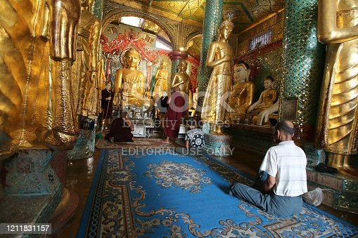Yangoon, Myanmar - January 27, 2020.  The pilgrims stop to meditate and pray in front of a sacred statue in the Pagoda.     Shwedagon Pagoda is the most sacred Buddhist pagoda in Myanmar, as it is believed to contain relics of the four previous Buddhas of the present kalpa.