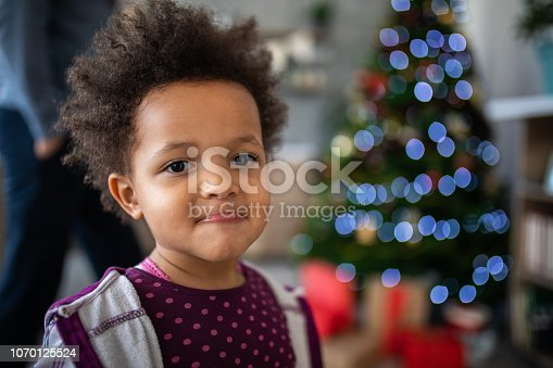 Shy little  Girl Enjoying Christmas Morning At Home