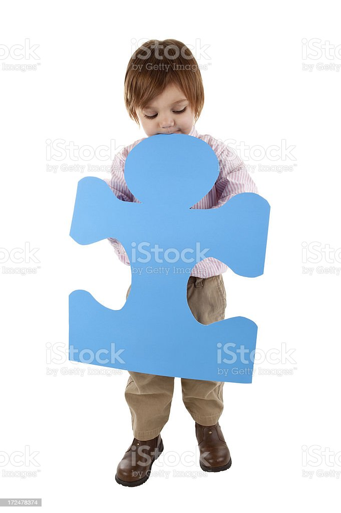 Shy Boy Holding Blue Puzzle Piece stock photo