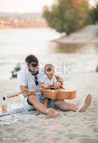 istock Shy boy learning from his father how to play a guitar 831372582