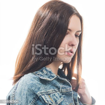 young shy brunet woman portrait in jeans jacket isolated on white background