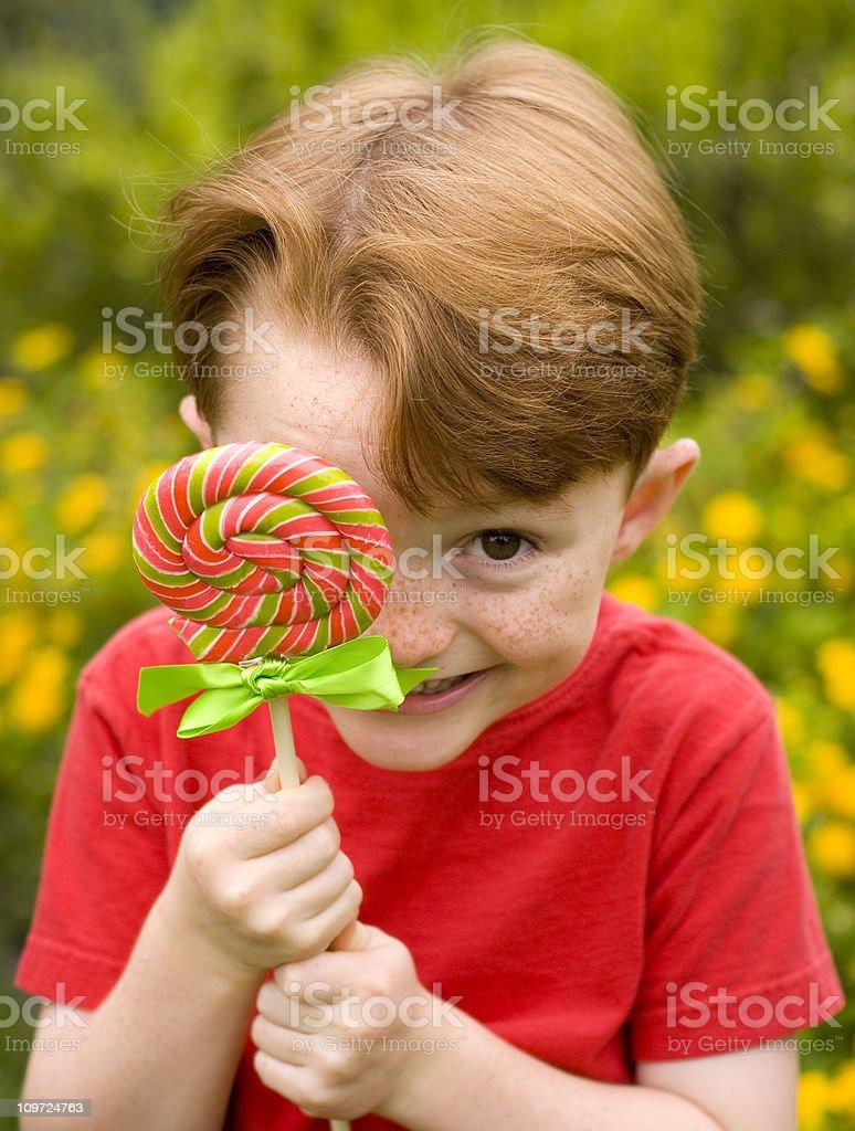 Shy Child in Flower Garden, Boy Hiding Behind Lollipop Candy royalty-free stock photo