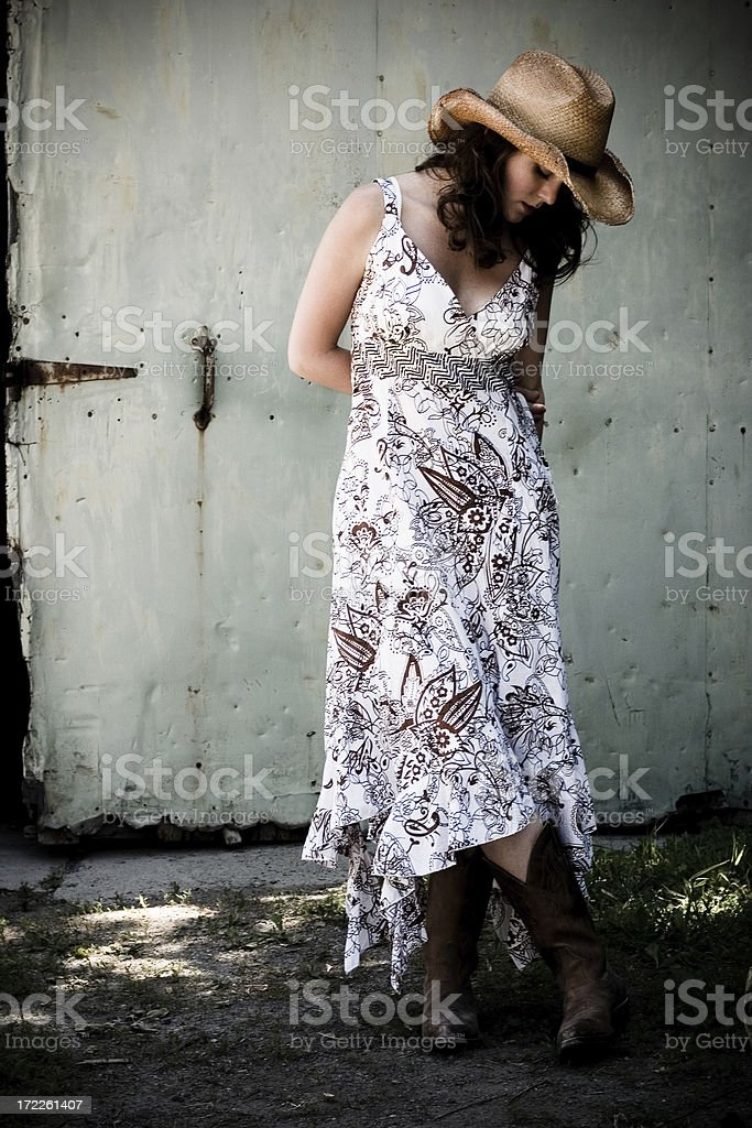 A shy country girl against a barn background royalty-free stock photo