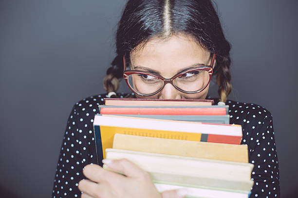 Shy dorky girl A lovely geek girl, true bookwork, hiding behind her pile of books nerd hairstyles for girls stock pictures, royalty-free photos & images