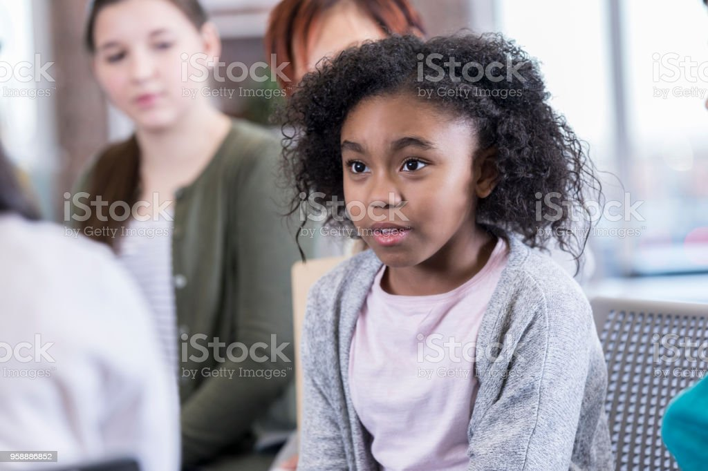 Shy elementary age girl speaks up in after school club stock photo
