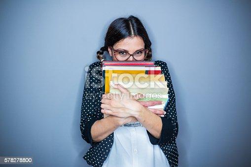 Nerd  girl holding some books , on gray background,hiding