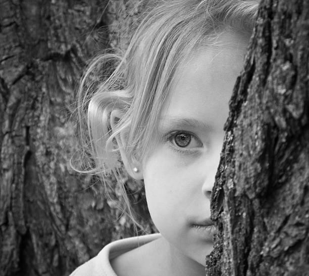 Shy girl, watching from behind a tree stock photo