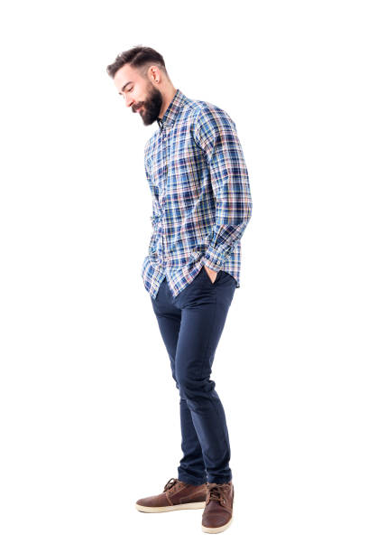 Shy handsome bearded young man in plaid shirt with hands in pockets smiling and looking down Shy handsome bearded young man in plaid shirt with hands in pockets smiling and looking down. Full body isolated on white background. hands in pockets stock pictures, royalty-free photos & images