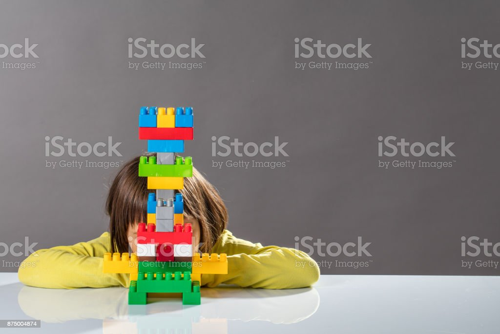 shy little child hiding behind built toy for kid psychology stock photo
