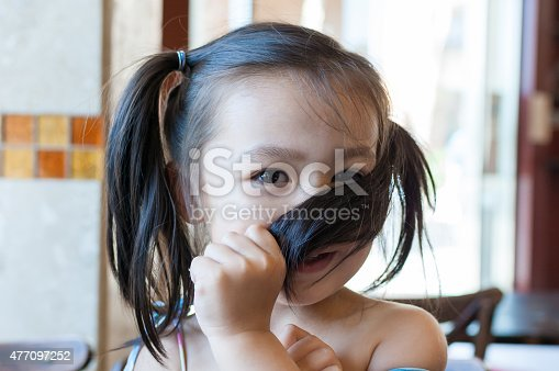 A cute preshool aged little girl pulls her hair across her face in a shy and humerous manner to cover her nose and cheek. She's located indoors in a resturant/coffee shop setting. The photo is a candid style, with a natural/authentic expression.