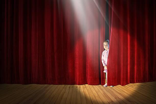 shy little girl on stage - mädchen vorhänge stock-fotos und bilder