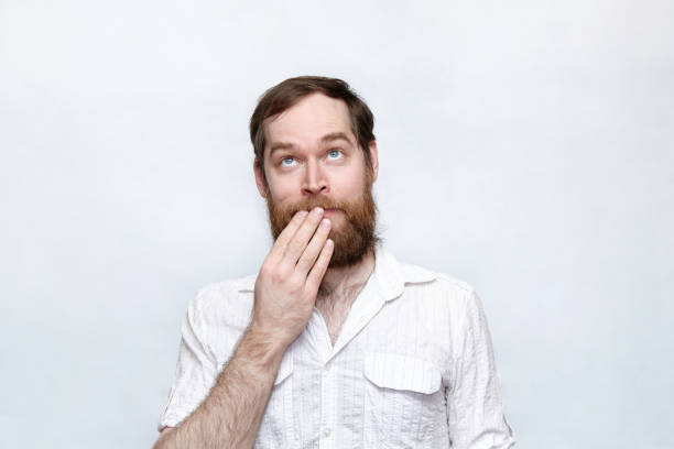 Shy man covering his mouth and looking up stock photo
