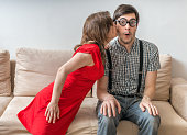 istock Shy man surprised by kiss from woman sitting on sofa. 623867684