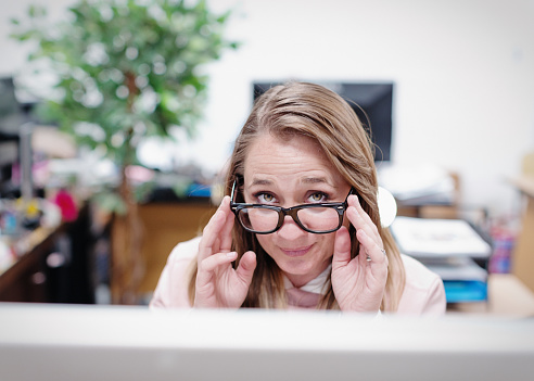 Woman sitting at computer looks over her glasses in an office.