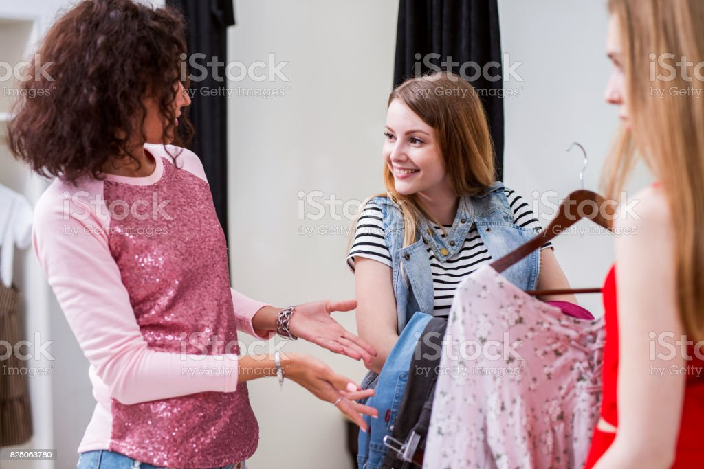 Shy smiling girl holding a pack of clothes listening to fashion stylist helping her picking outfit in a changing room stock photo