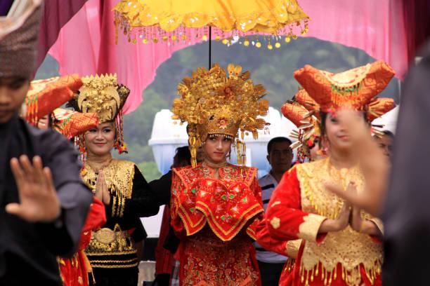 Shy traditional Minang dancer looking at crowd stock photo