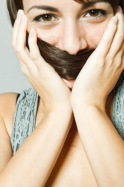 shy woman with hair infront of face stock photo