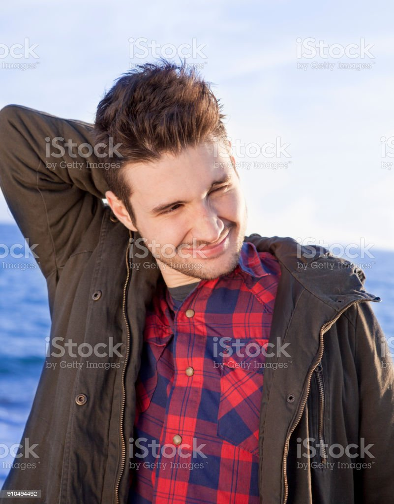 Shy young latino man in front of the sea stock photo
