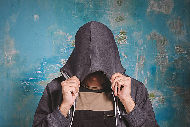 Shy young man closing his face Portrait of shy young man closing covering his face with hands and hoody can't see, hiding. Antisocial and negative human emotion facial expression feeling reaction embarrassment stock pictures, royalty-free photos & images