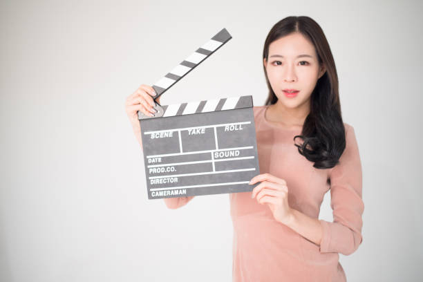 sian woman holding movie clapper board isolated on white background. cinematography, communication arts, casting, audition, movie production concept. - audition stock photos and pictures