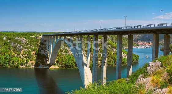 Sibenik Bridge across canyon of the Krka River. Panoramic view towards Scradin town, North Dalmatia, Croatia. Cliffs of coastline.