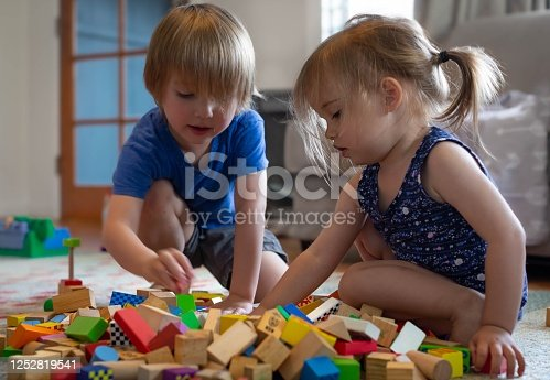 Little boy and girl playing together with toy blocks at home.