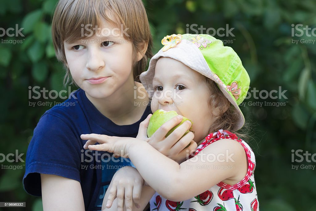 Sibling children sharing green apple fruit outdoor stock photo