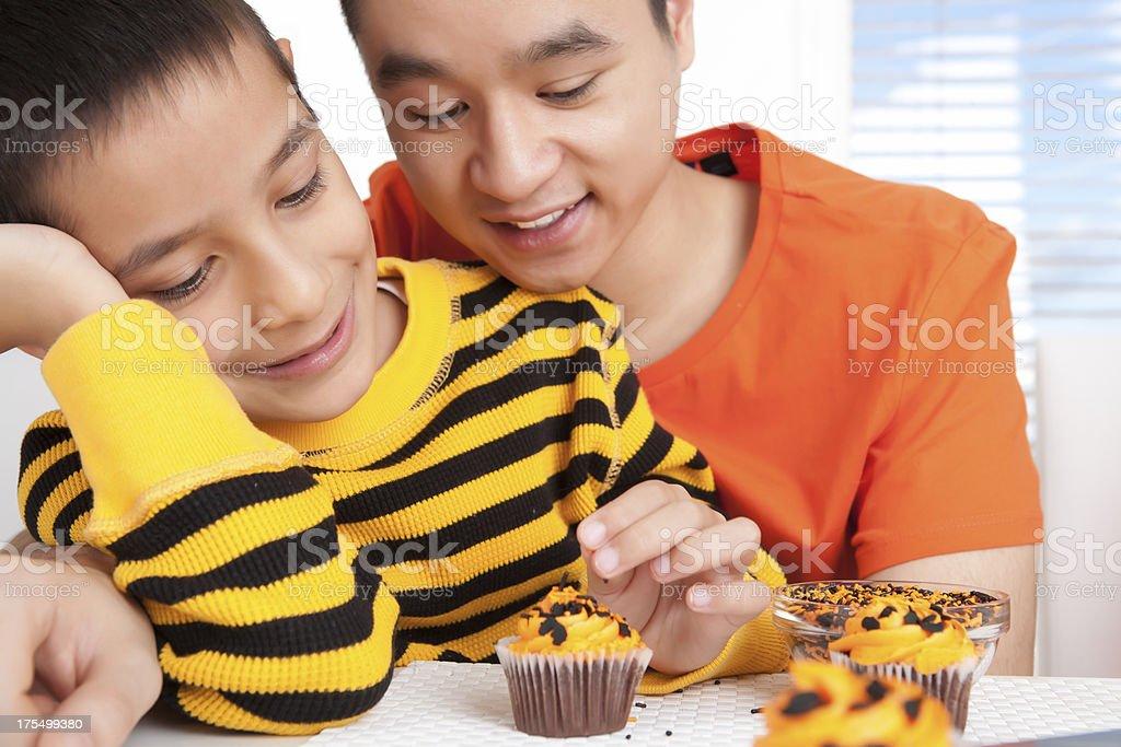 Sibling decorating halloween cupcakes royalty-free stock photo