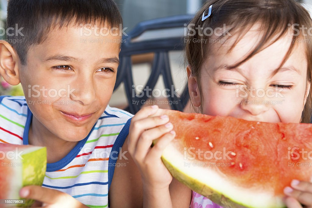 Sibling eating watermelon outdoor royalty-free stock photo