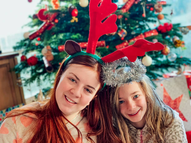 Sibling Love on Christmas Day Two sisters are sitting side by side, looking towards the camera and smiling. It is Christmas Day, they are both in their pyjamas and wearing dress up, festive headbands. 12 17 months stock pictures, royalty-free photos & images