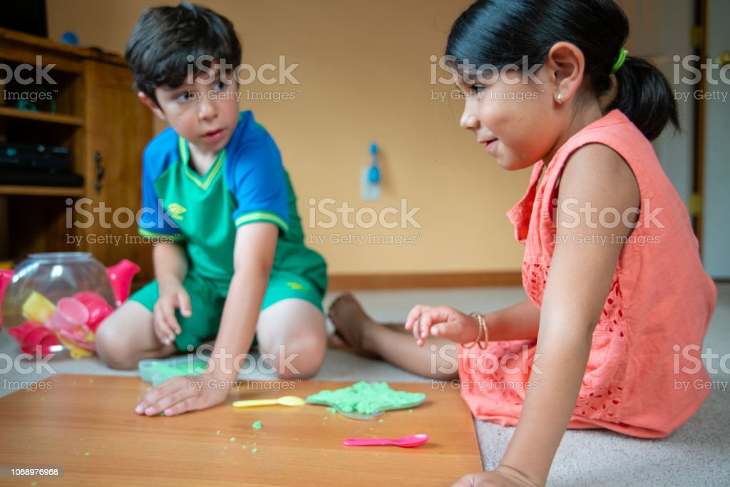 Sibling. The little brother and sister, the 8-years-old boy and 6-years-old girl, playing with the green colored toy sand on the floor in the children's room stock photo