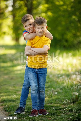 Smiling brother hugging his little sibling in a park
