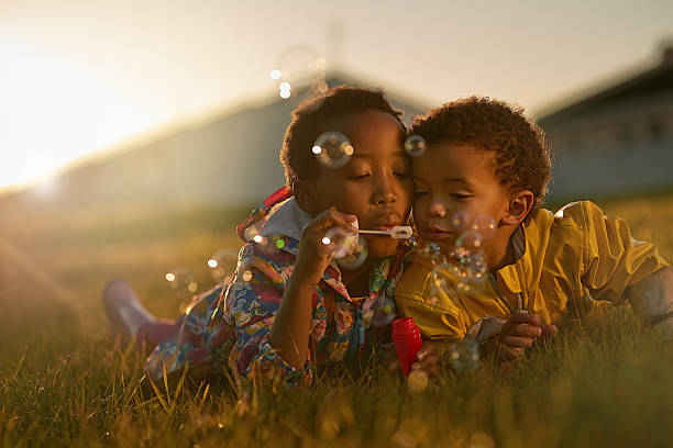 Siblings and the best of friends Shot of a brother and sister lying on the ground outside blowing bubbles brother stock pictures, royalty-free photos & images