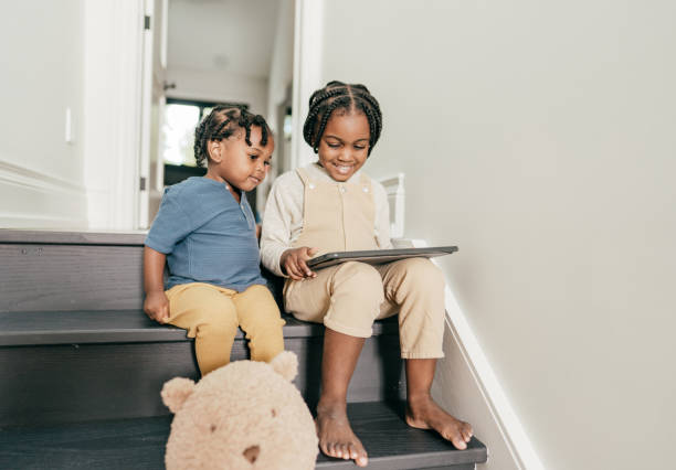 Siblings at home using tablet stock photo