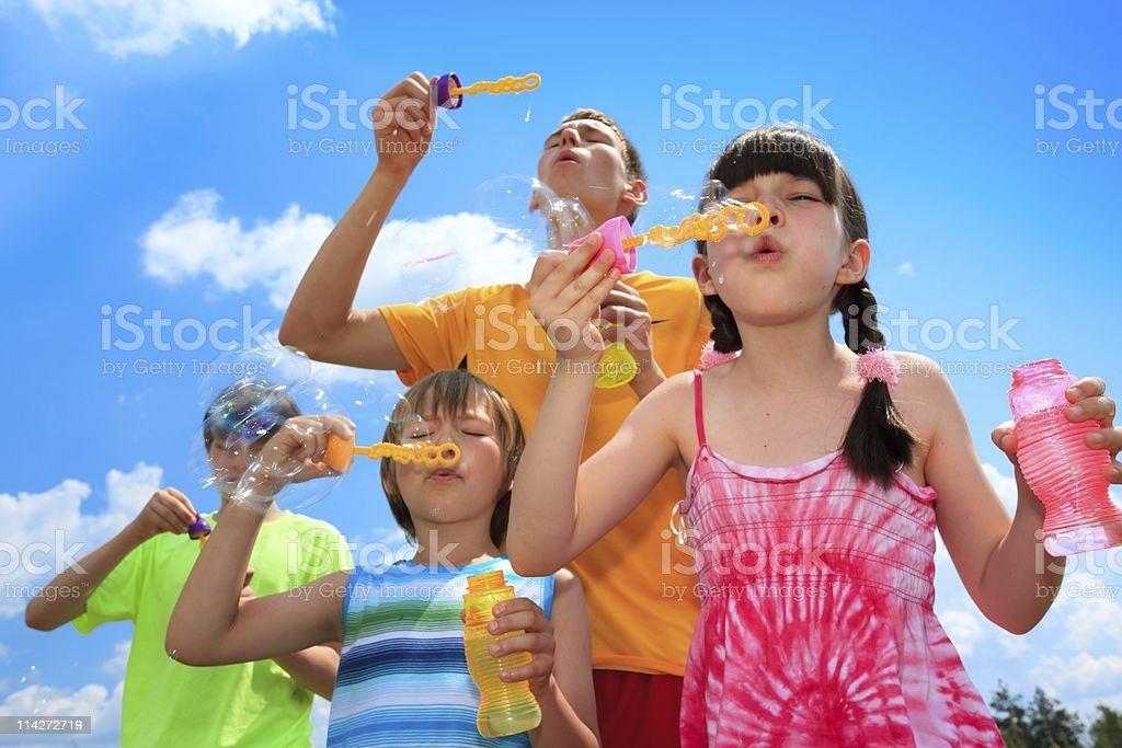Siblings blowing bubbles royalty-free stock photo