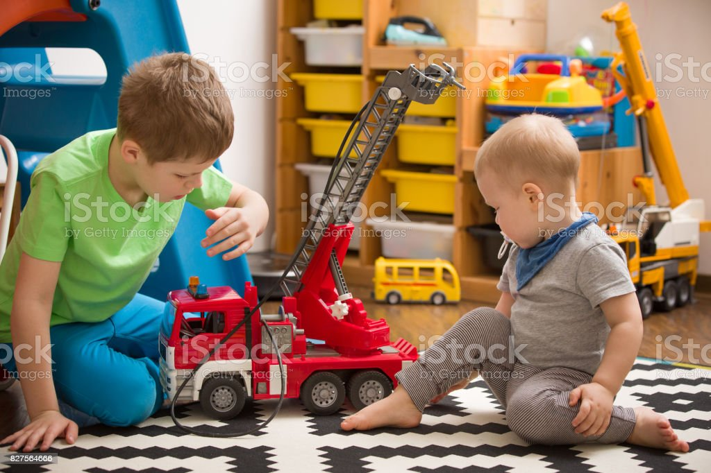 Siblings boys playing with a toy fire truck in kids room. Children...