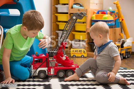 184659330 istock photo Siblings boys playing with a toy fire truck in kids room. Children playing cars in their room. Leisure activities at home. Playground. indoors. Profession. Fireman. 827564666