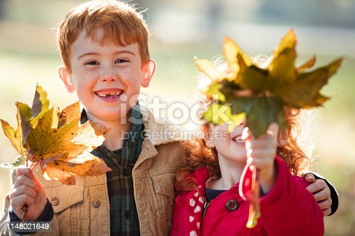 Portrait of two children in a public park holding leaves which they have collected.