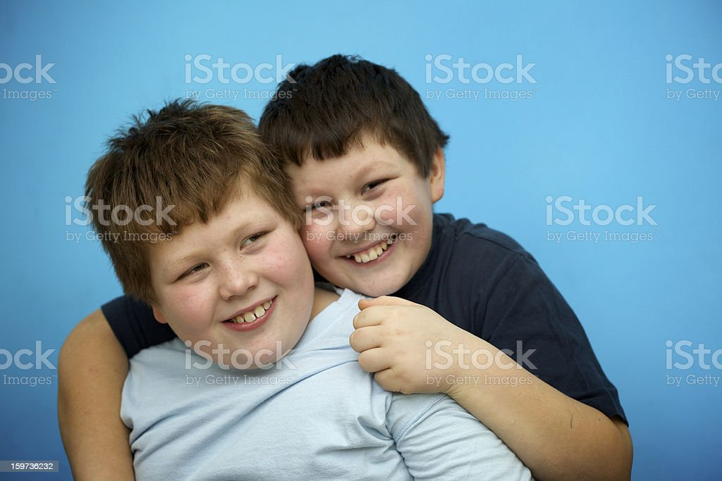 siblings: cute overweight boys hugs in front of blue wall royalty-free stock photo