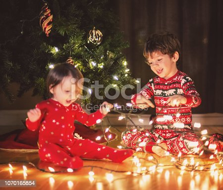 Brother and sister decorate their Christmas tree together.