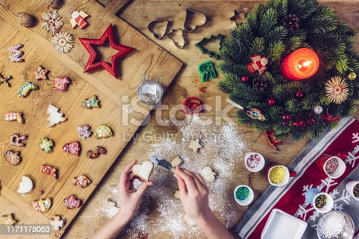 overhead view on siblings decorating christmas cookies together on rustic wooden table