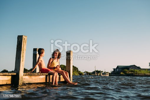 Siblings dipping feet in water on pier at Outer Banks, North Carolina.